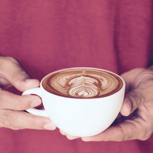 a cup of cappuccino coffee with beautiful latte art in man hands, wearing red t-shirt, vintage tone